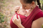 Mother carrying her cute baby daughter in sling, kissing her, outside in autumn nature